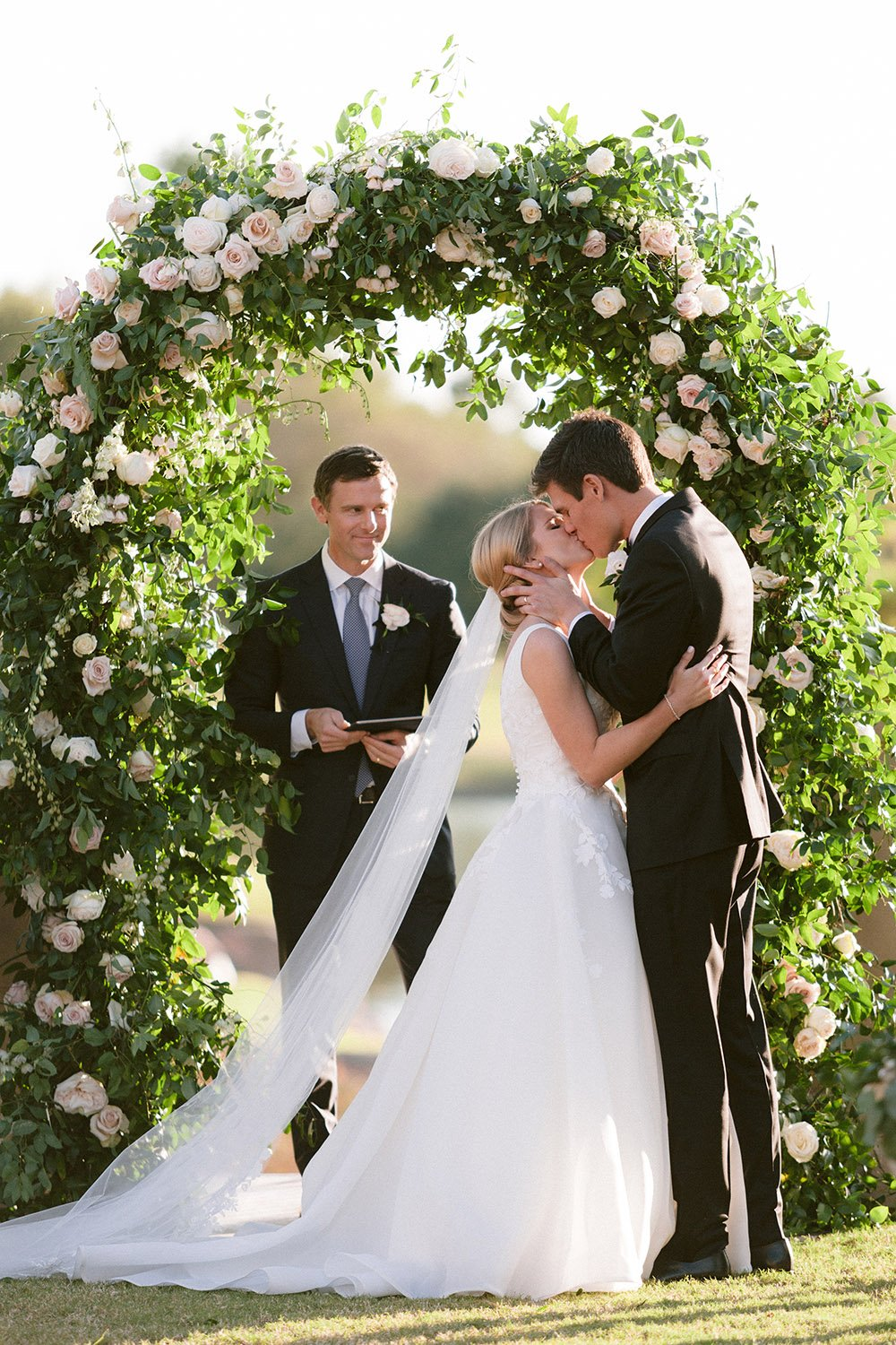 Bride, in long white gown and flowing veil, kisses the groom, in a black tuxedo, underneath a greenery and rose covered arbor on the lawn at Royal Oaks Country Club in Houston.