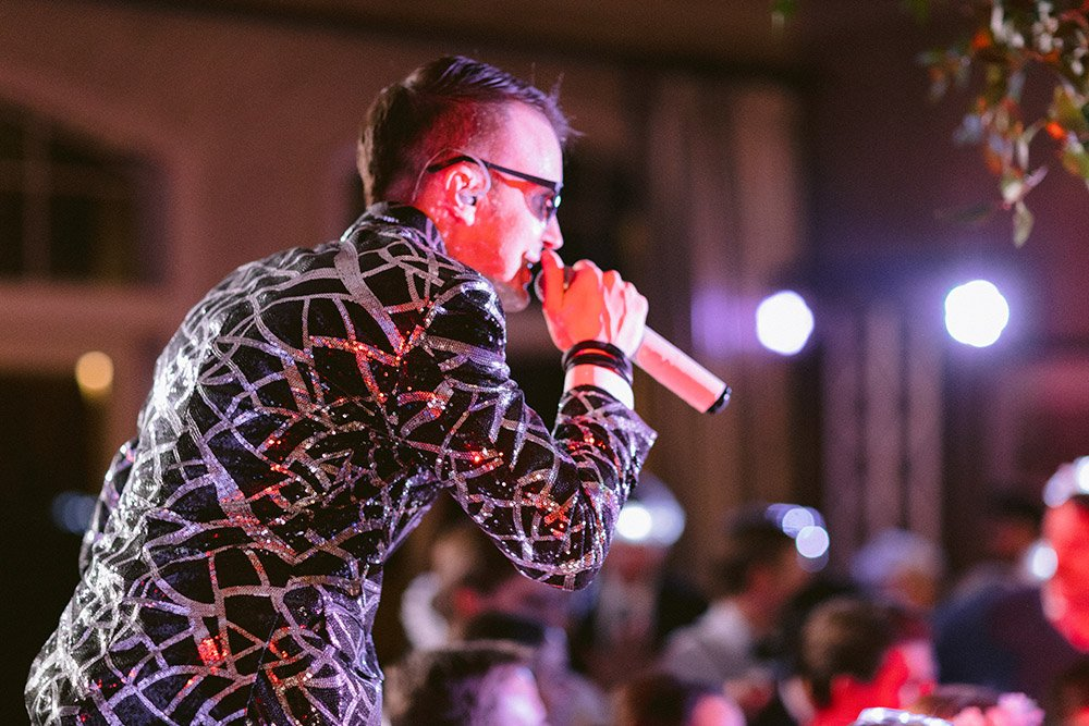 Danny Ray, in sequin black and silver jacket, speaks directly into a microphone during a wedding reception at Royal Oaks Country Club.