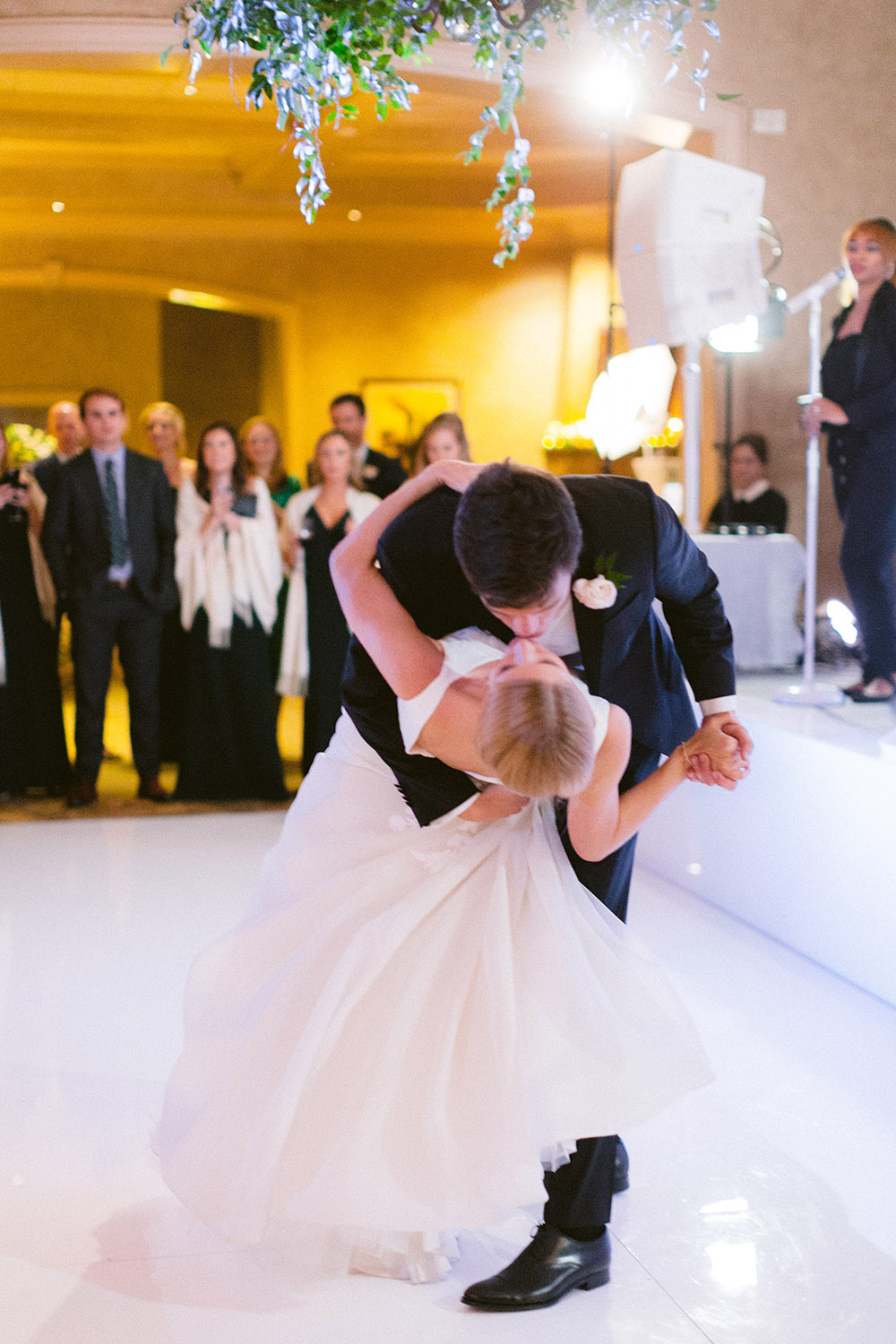 Groom kissing bride on a white dance floor amidst lush hanging greenery