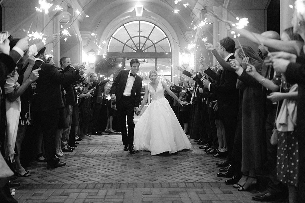 Groom and bride holding hands and smiling during the sparkler send off at Royal Oaks Country Club.