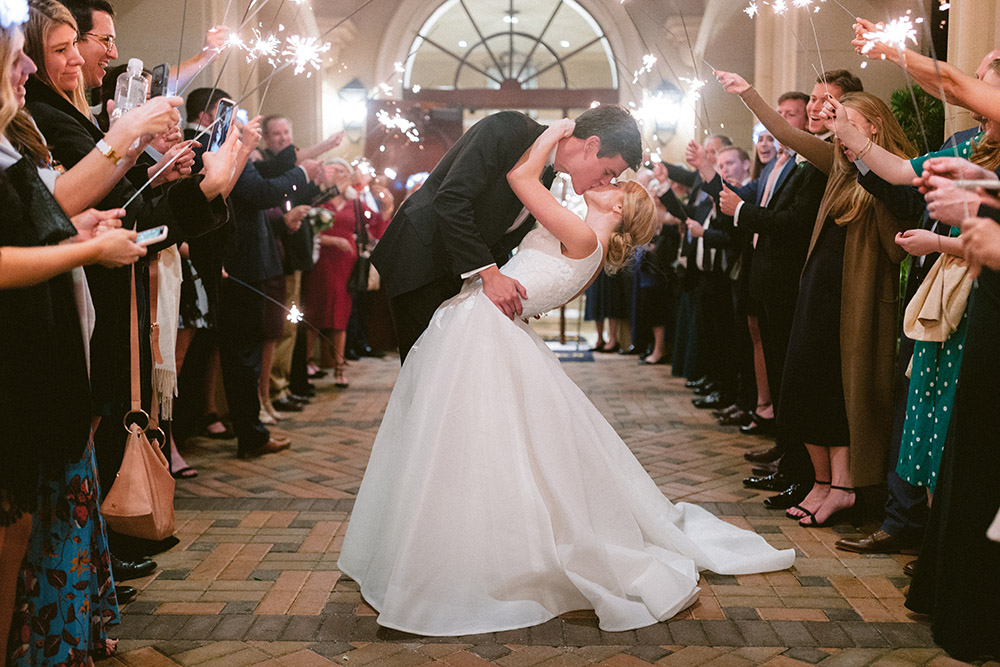 Bride and groom kissing during a sparklers send off on the outside patio of Royal Oaks Country Club.