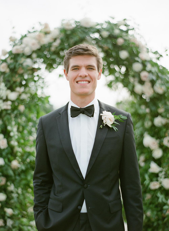 Groom in classic black tuxedo with black bow tie.