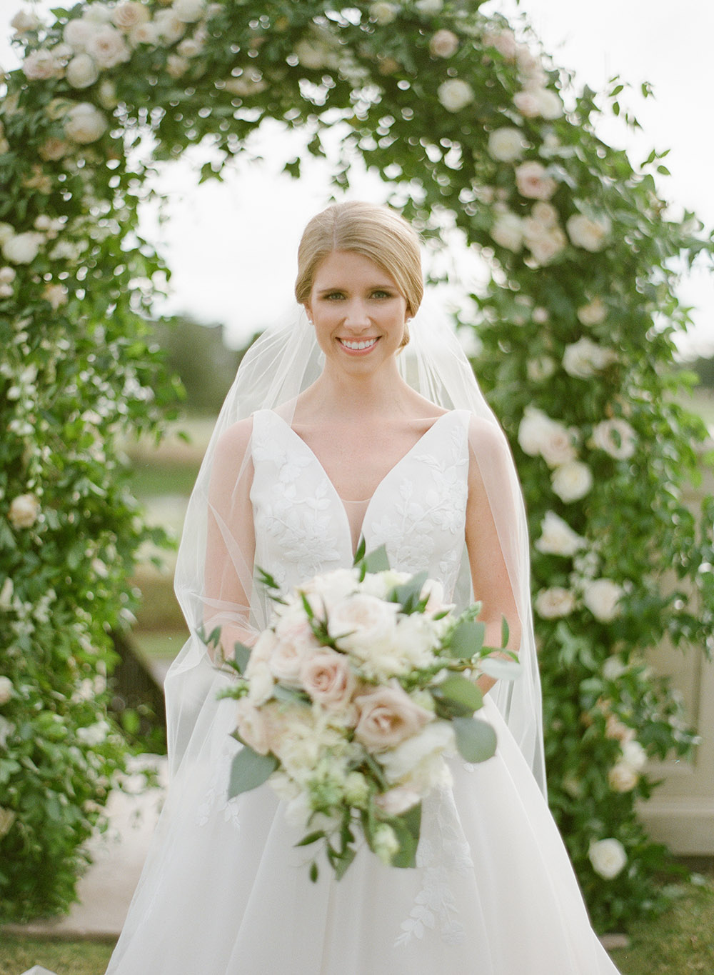 Bride, wearing white sleeveless gown with lace embroidery and long veil, standing in front of greenery arch covered with blooming blush pink roses.