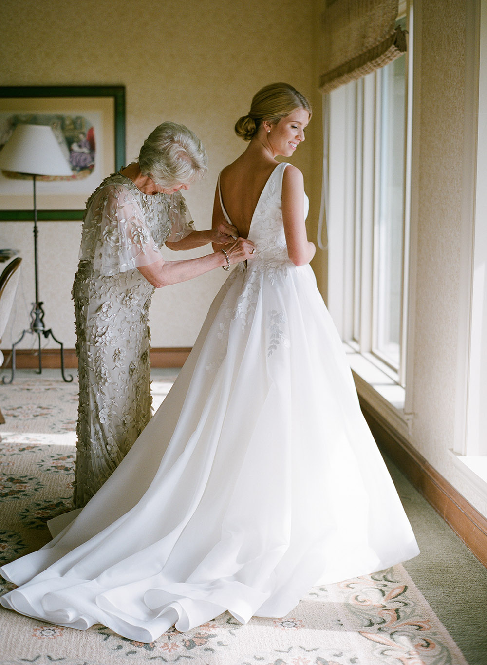 Bride getting ready while her mother helps her in her elegant and classic white wedding dress.