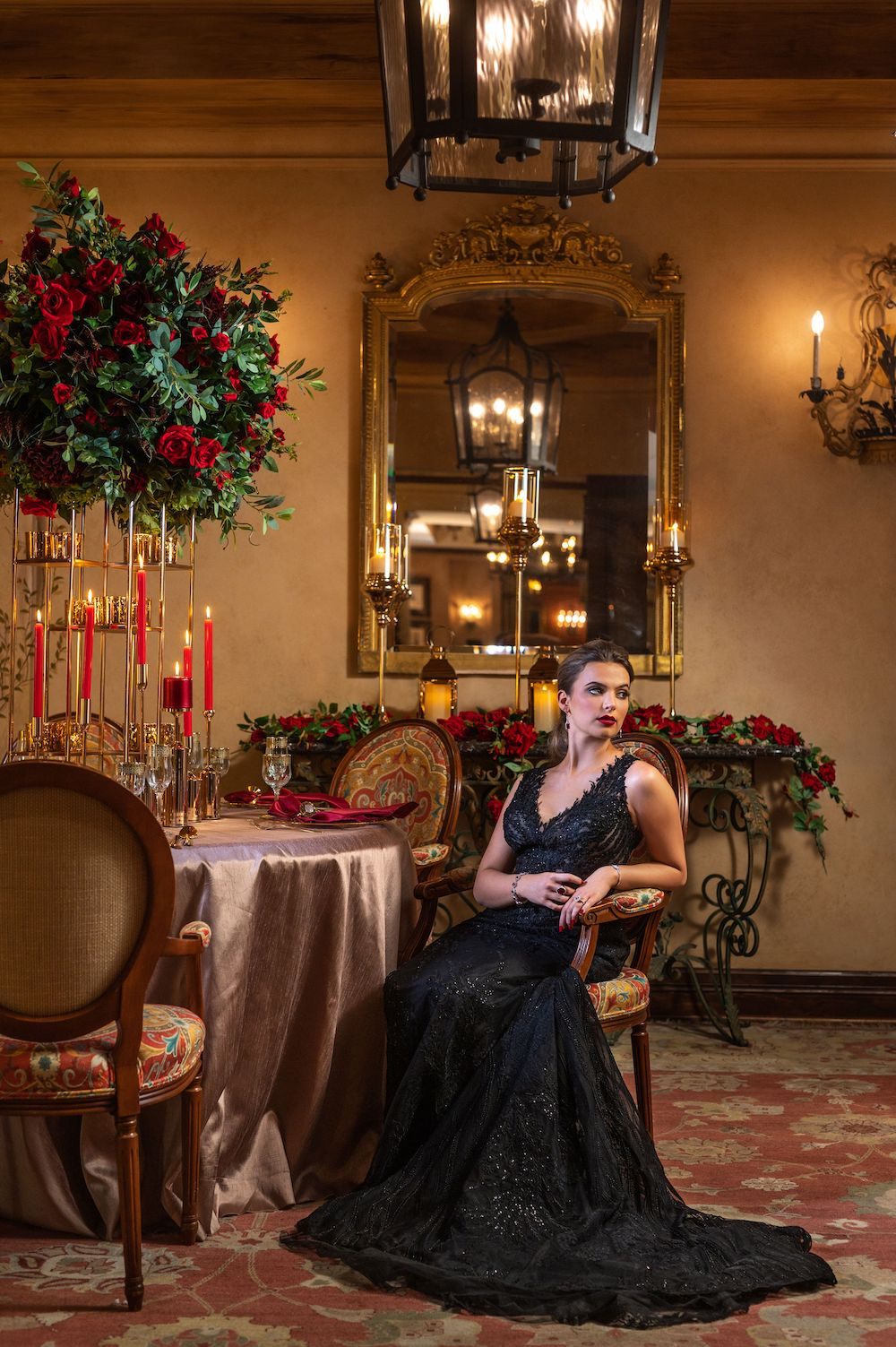 Bride with red lips, black smokey eye makeup and ponytail in sleeveless black wedding gown seated at table with tall blooming red rose centerpiece, red pillar candles with gold candleholders, and metallic table skirt inside of ballroom of Hotel Granduca Houston.