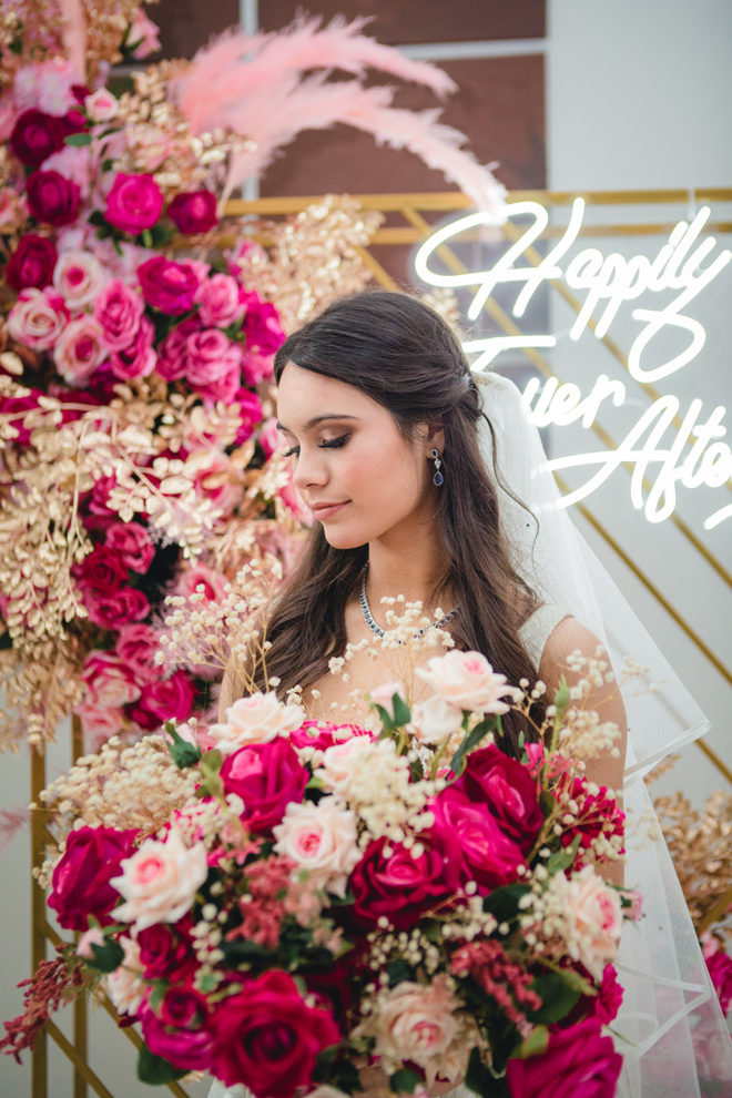 """Bride, holding hot pink, blush and ivory bouquet of roses, with hair tied back with veil, amongst hot pink, gold and blush plumes adhered to a gold backdrop with an LED sign that reads, """"Happily Ever After"""" in the ballroom of Hyatt Regency Hotel Houston."""
