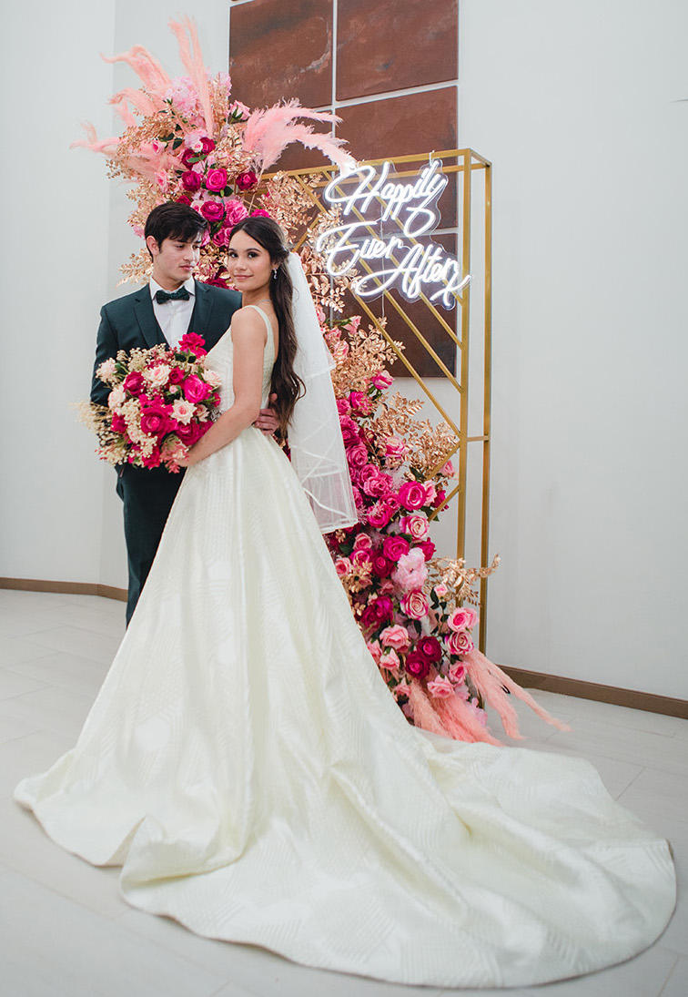 The bride and groom stand in front of a city chic photo backdrop adorned with fuchsia, blush, and gold florals.