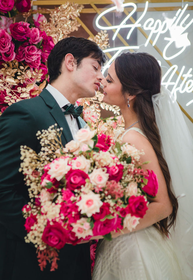 """Groom leaning in to kiss the bride, holding a bouquet of blush, fuchsia and ivory silk florals, with LED sign in the background which reads, """"Happily Ever After"""" in ballroom of Hyatt Regency Houston."""