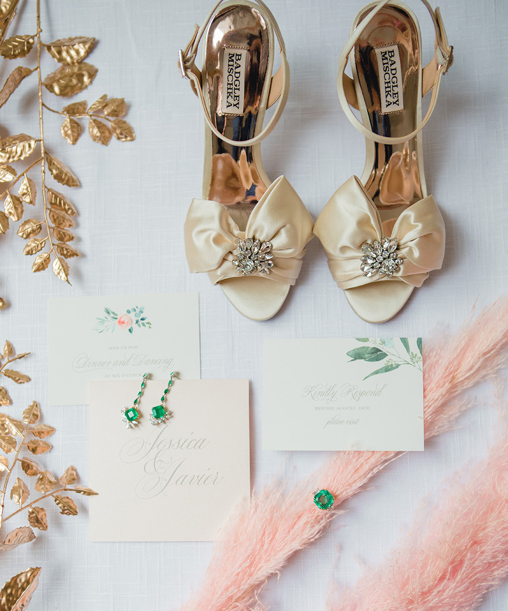 Wedding invitations rest atop white canvas surrounded by gold and blush foliage, gold heels, and emerald jewelry.