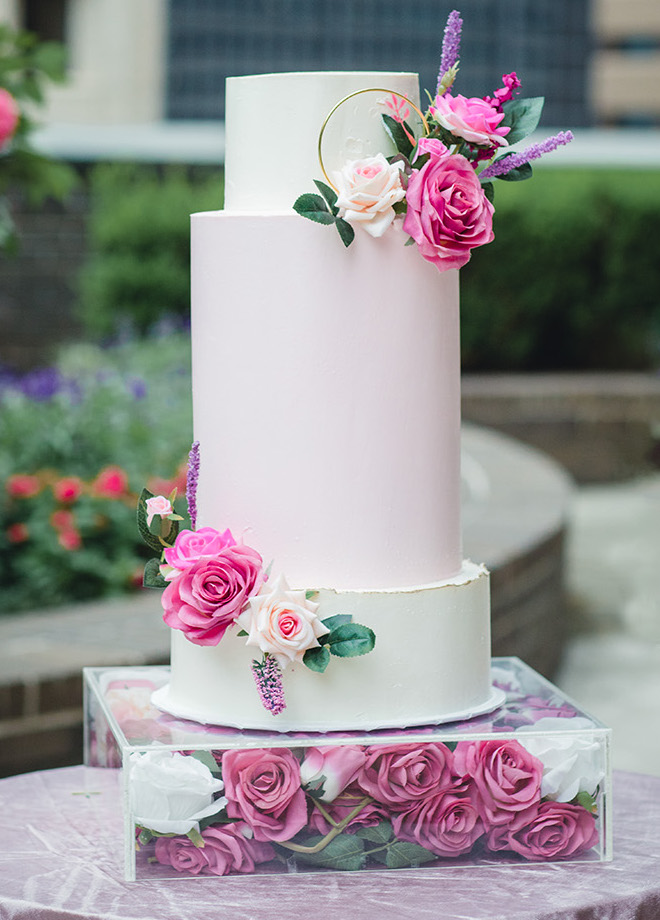 A three-tiered wedding cake features layers of various heights and floral accents.