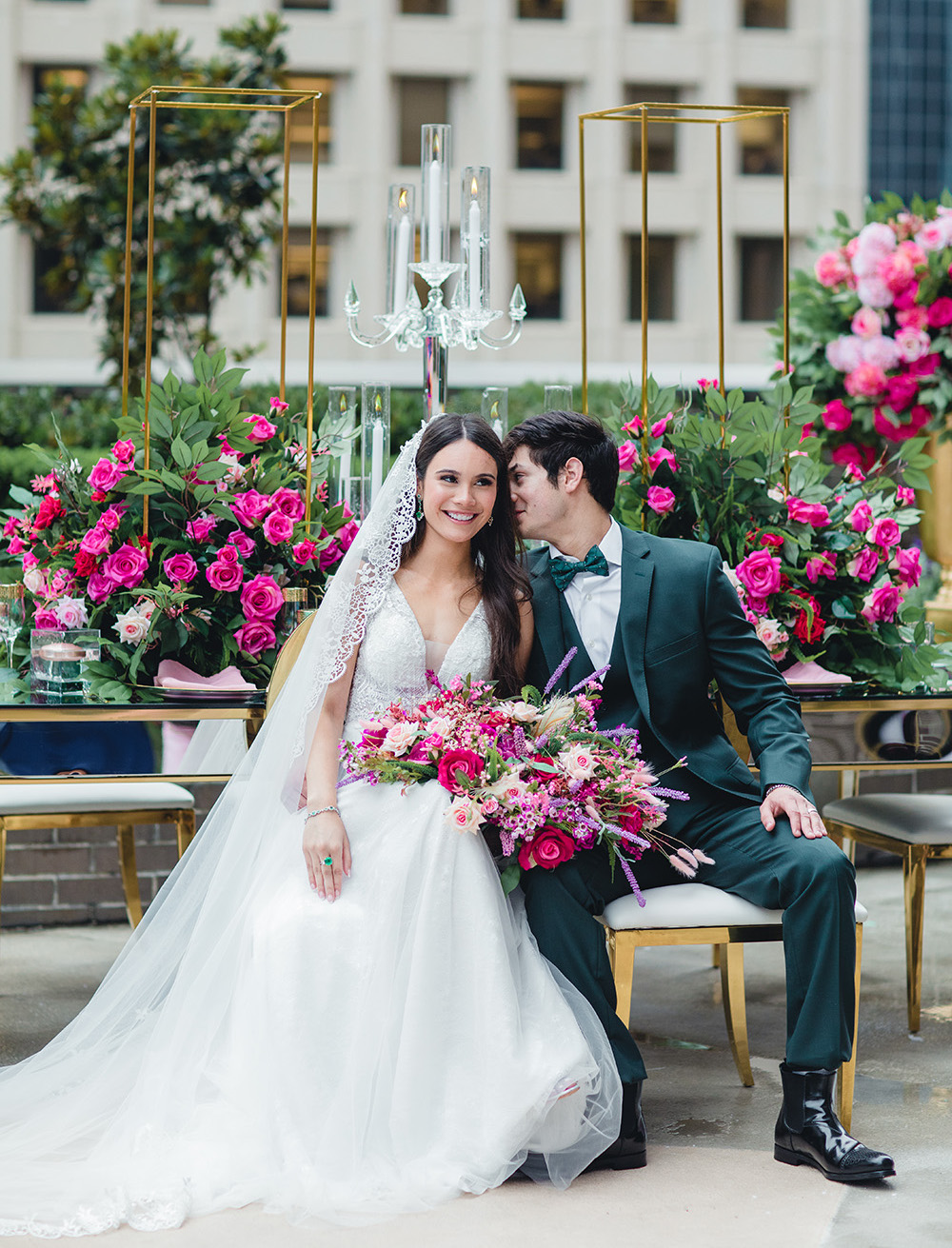 The groom in an emerald suit whispers sweet nothings to his bride while she holds her vibrant bridal bouquet.
