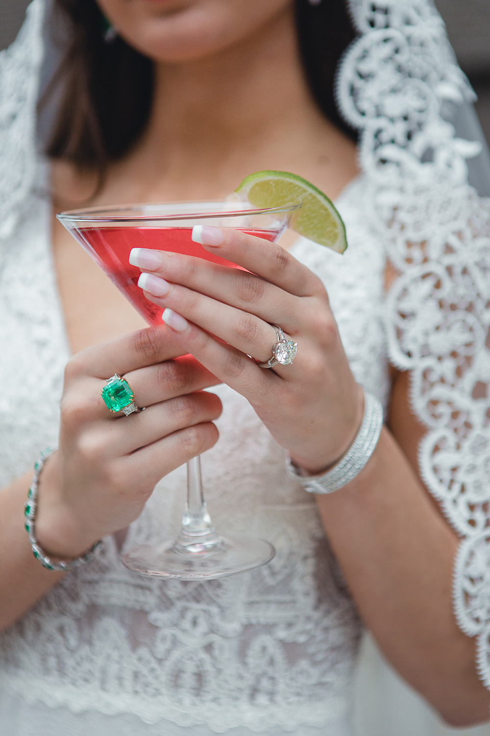 Our bride dons her gorgeous emerald and diamond wedding jewelry while holding a pink cocktail with a lime sliver.