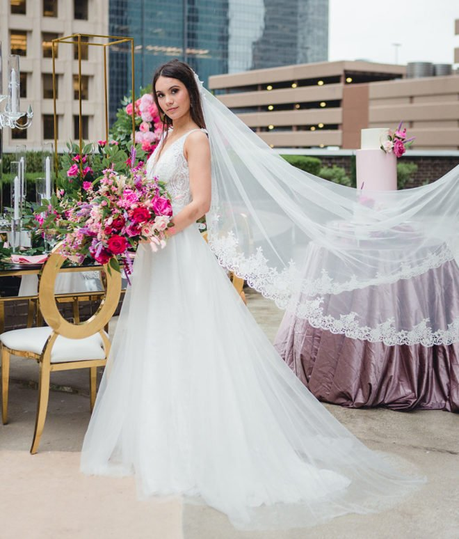 Bride, on the outside garden and patio of Hyatt Regency Hotel Houston, holding blush and hot pink bouquet of florals, in long white tulle gown with long formal veil flowing directly behind her.