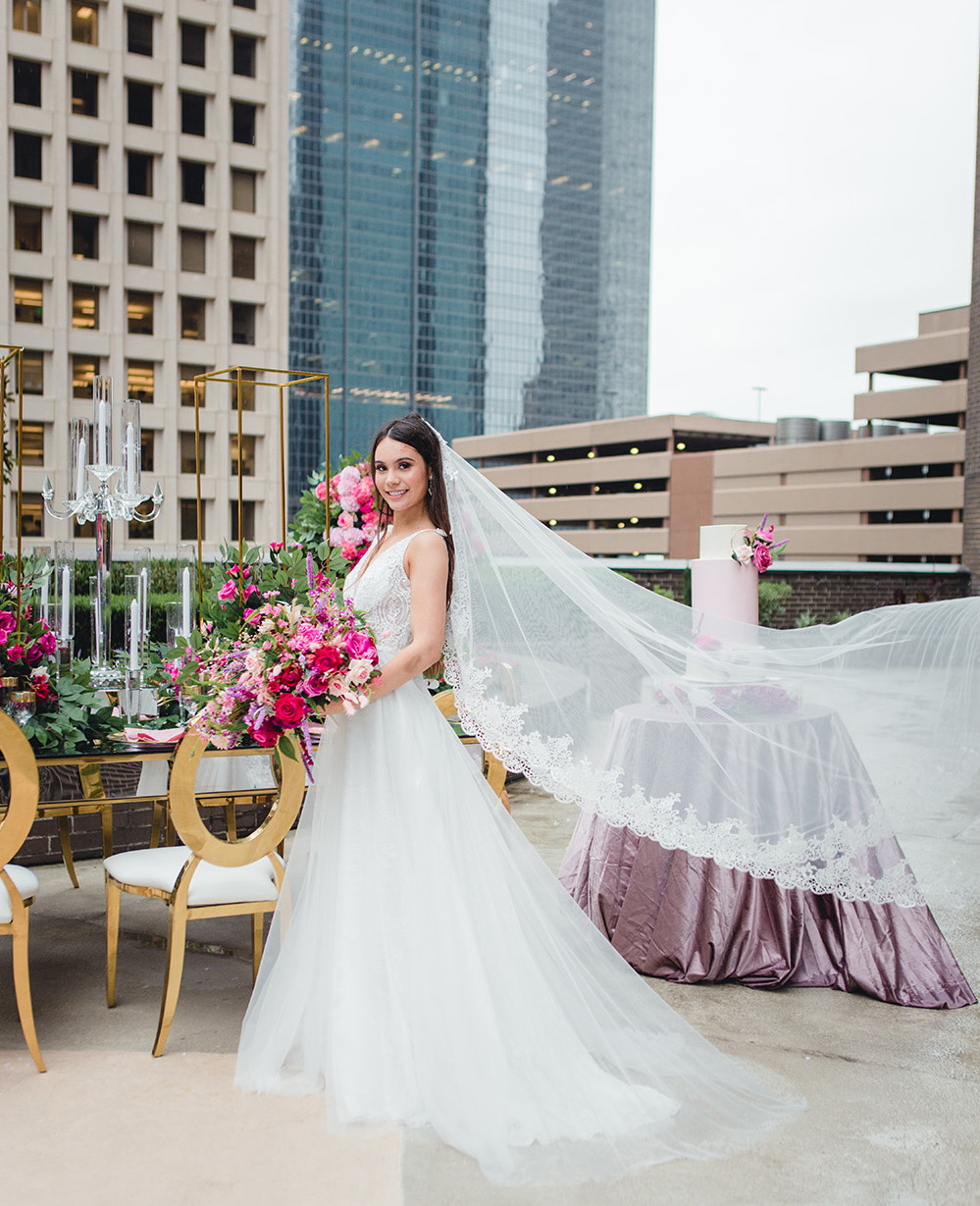 Our bride holds her bridal bouquet in front of a reception table while her veil gracefully catches the wind.