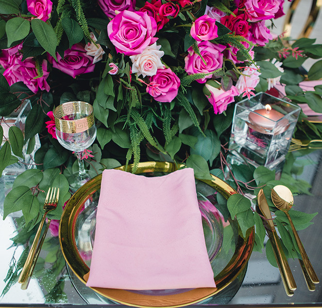 Vibrant, city chic wedding flowers in bright pink and blush flow across the table accenting gold glassware, dishware, and flatware.