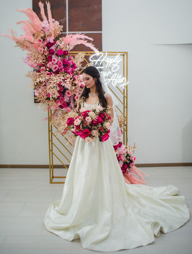 """Bride holding bouquet of hot pink and blush florals with gold backdrop accented with lush blush colored plumes, coordinating hot pink and blush florals, gold leaves and LED sign which reads, """"Happily Ever After"""""""