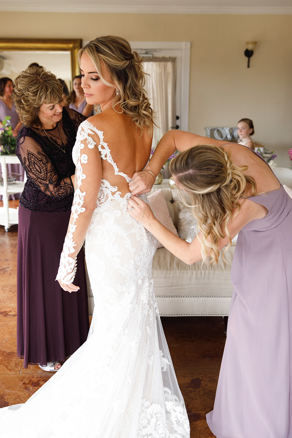 Mother of bride and bridesmaid helping bride into her long-sleeved lace gown.