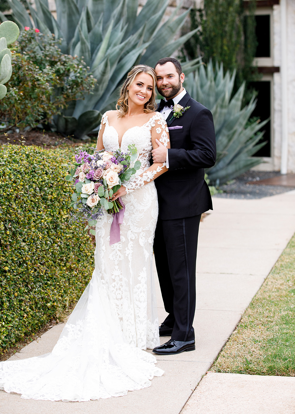 Bride in a romantic long sleeved lace gown with sleek lengthy rain and lilac lush bouquet, and groom in a classic black tux.