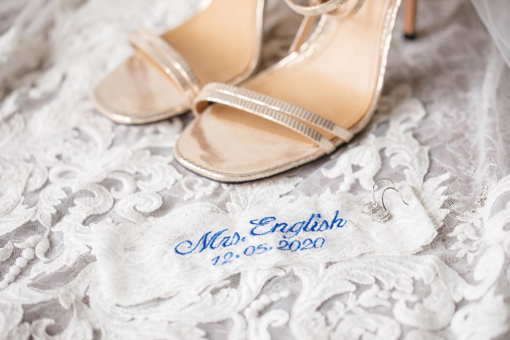 Silver wedding shoes accompanied by a laced and monogramed garter.