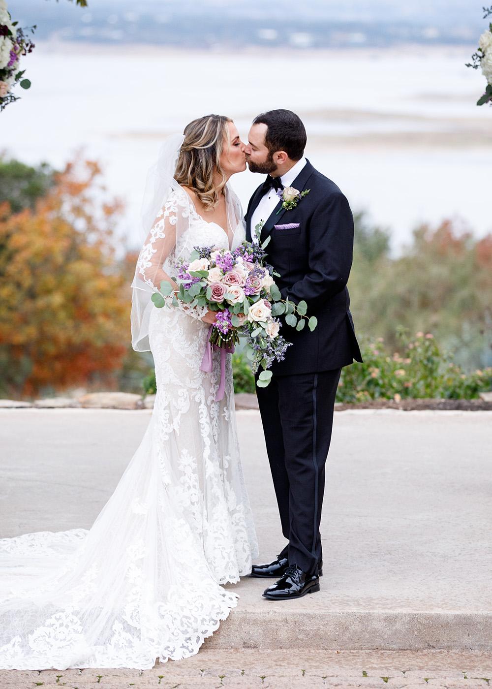 Bride and groom's first kiss lake front at Lake Travis.