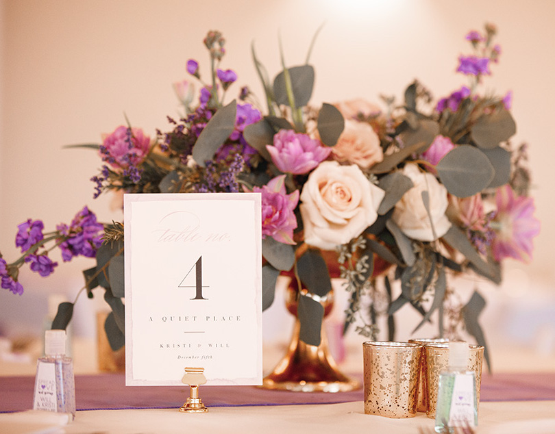 Romantic floral table decor including rose gold roses, lavender, eucalyptus and violet hydrangeas by Malleret Designs.