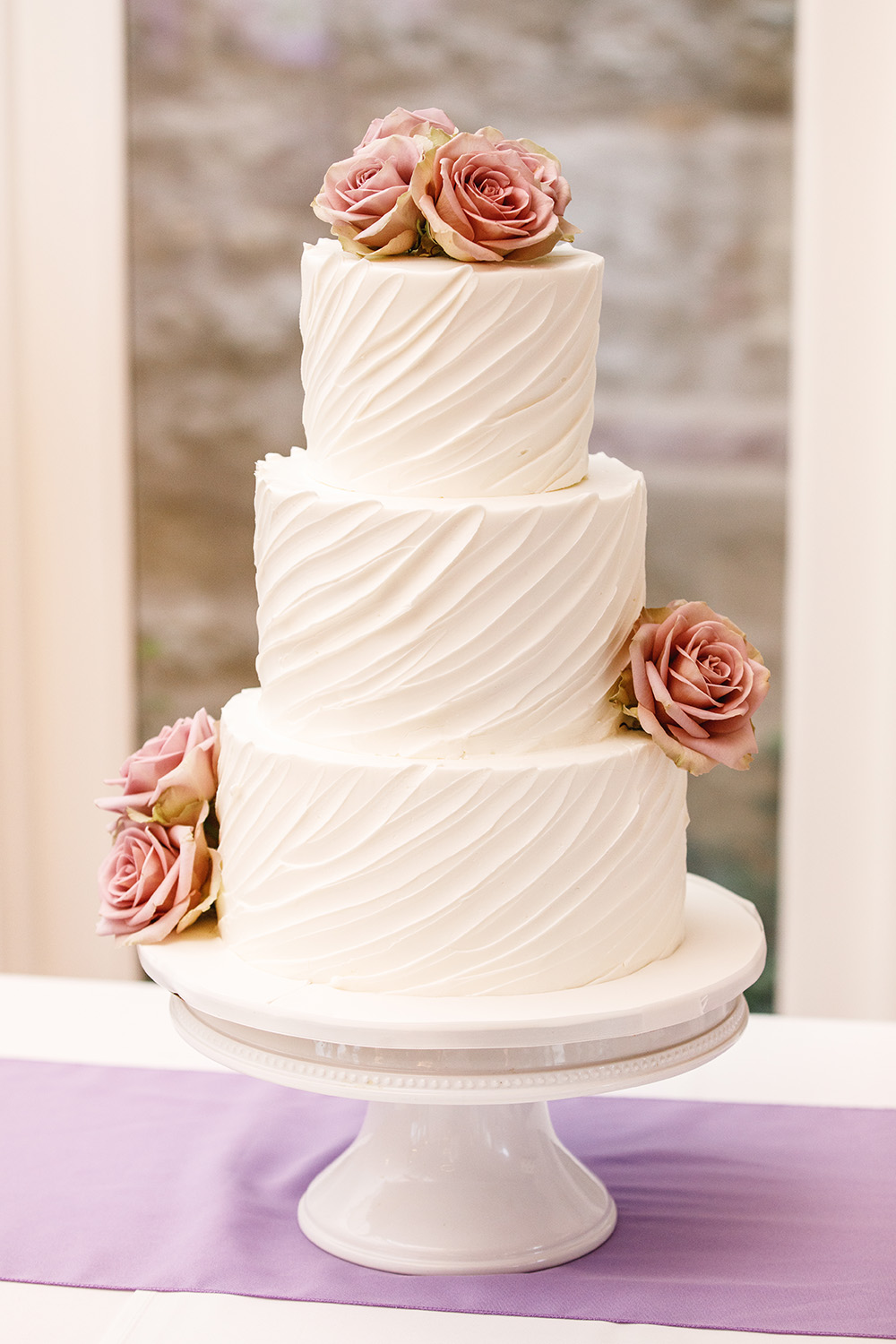 3-tiered buttercream cake with lilac florals.
