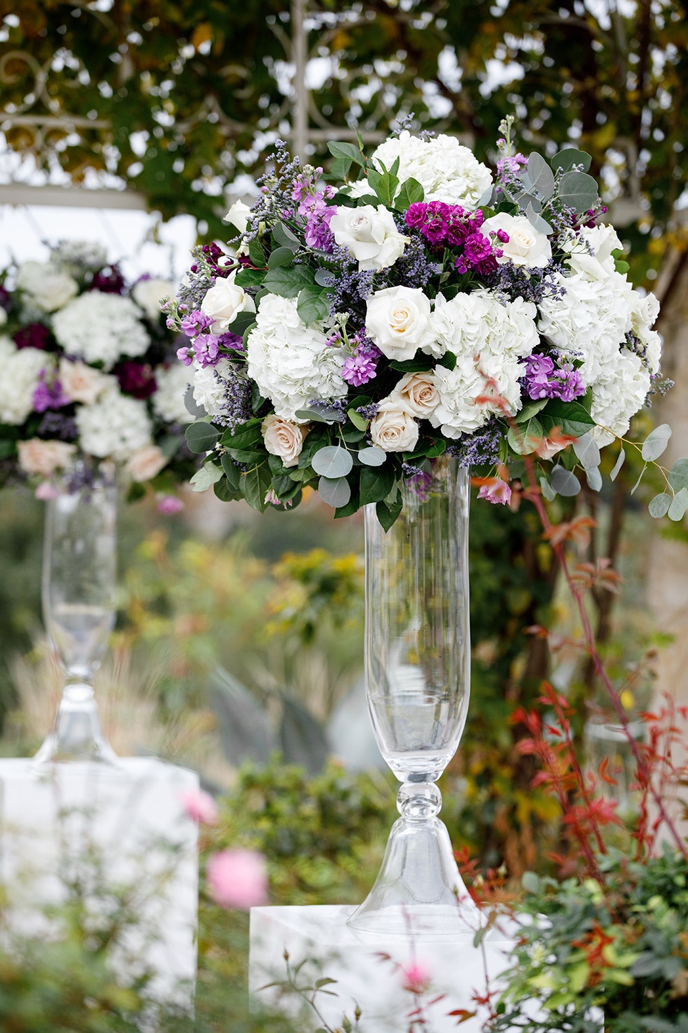 Ceremonial floral arrangement with a mix of white and lilac roses and hydrangeas.