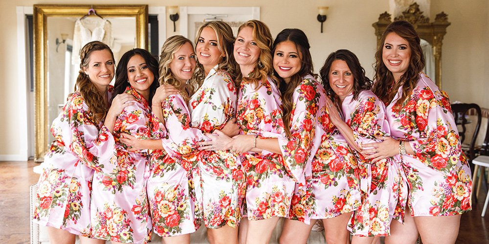 Bridesmaids in matching floral pink silk robes prepping for a wedding ceremony.