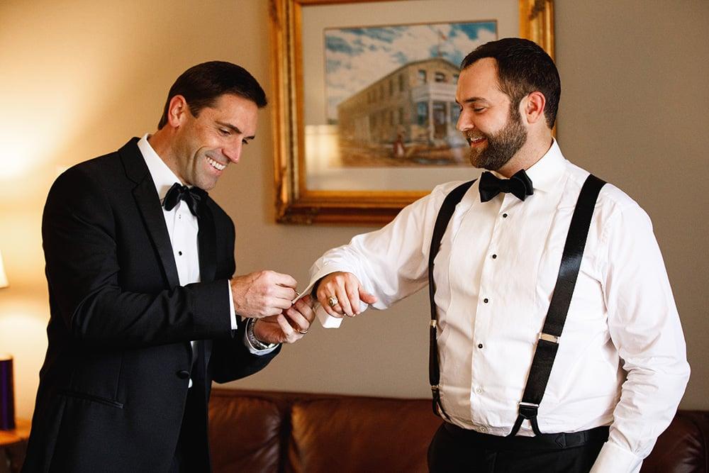 Groomsman helping groom with his cufflinks for his wedding.
