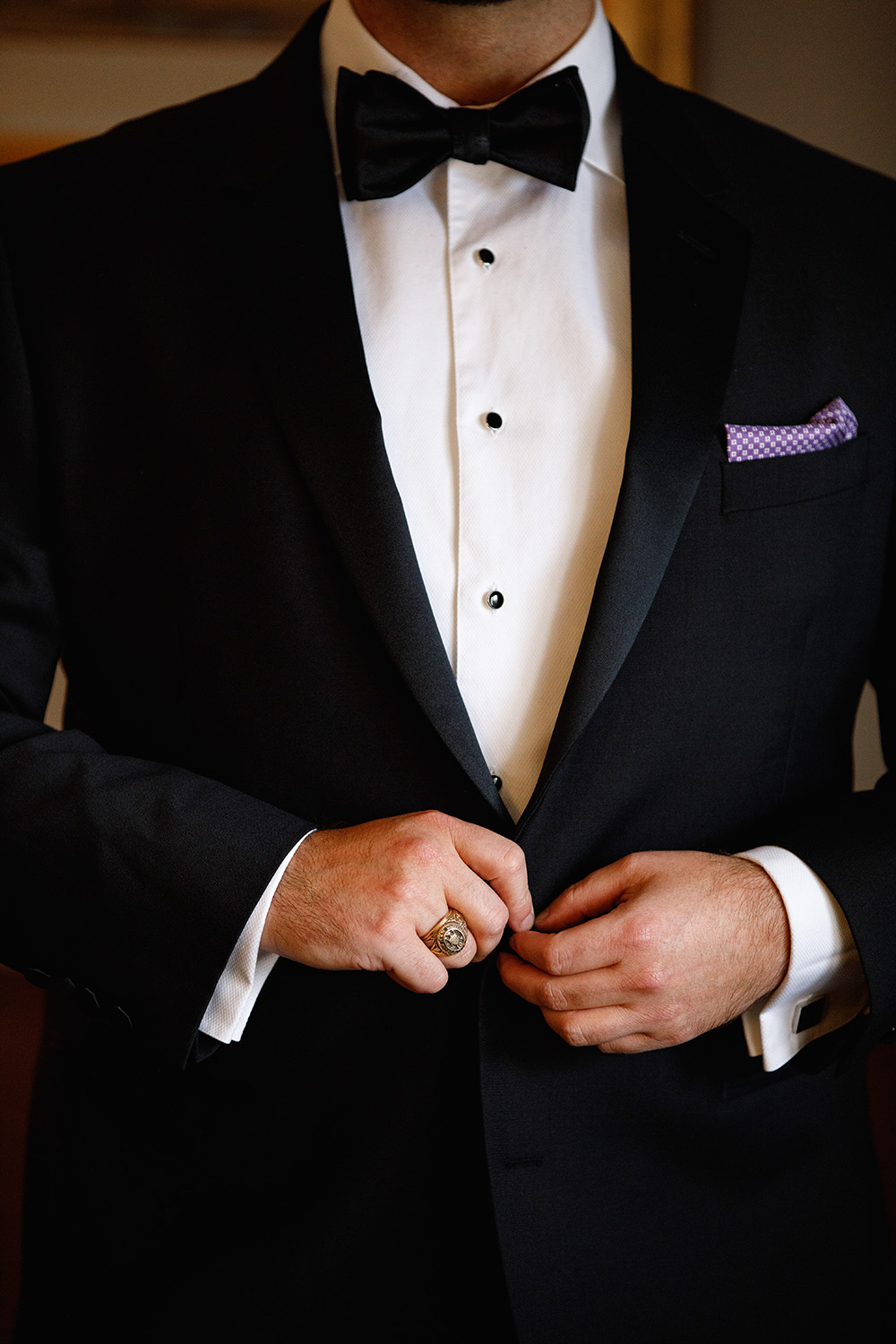 Classic tuxedo with black bow tie and pattered violet pocket square.
