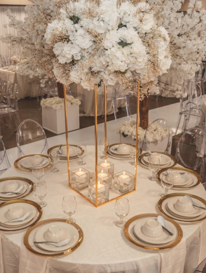 Wedding guest table decorated in gold and ivory placesettings with lush blooming floral centerpiece with beige, white and ivory florals by Mod Effect Events