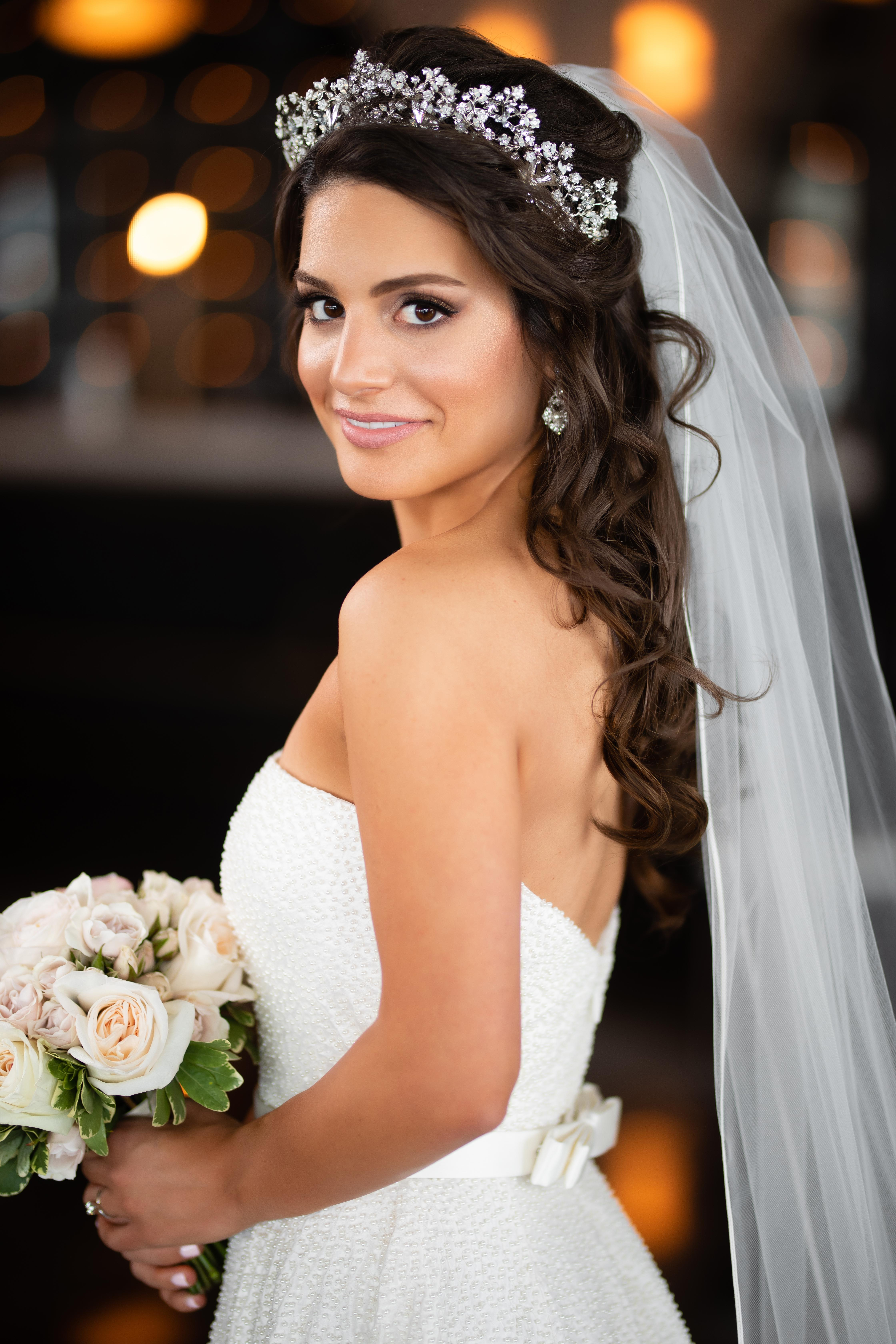 Bride with crown and long bridal veil with a classic white dress and ivory rose bouquet.