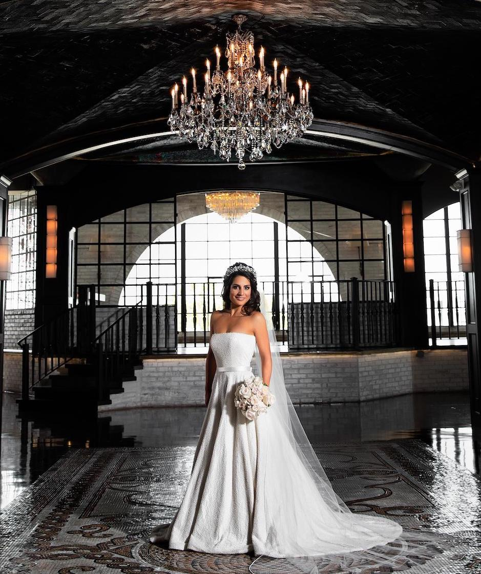 Bride at the Astorian with chandeliers hanging above.