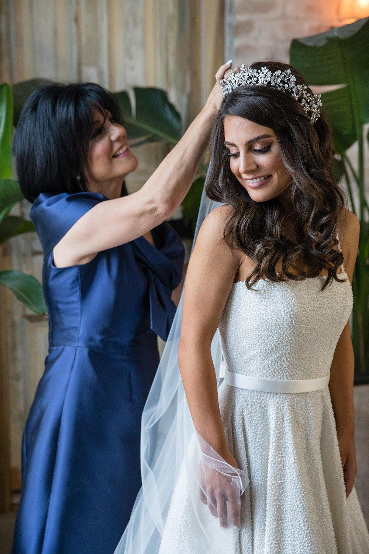Mother of the bride adjusting her daughters veil.