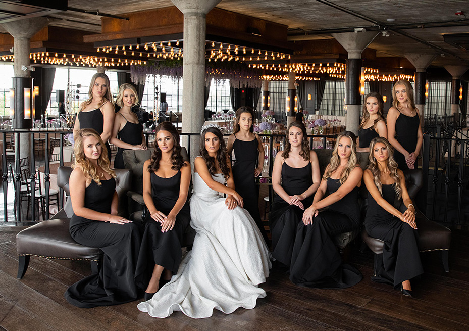 Bride and bridesmaids in fitted black floor length dresses at The Astorian.