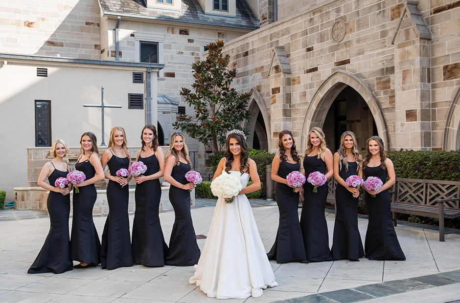 Bridesmaids hold bouquets that match the lavender, violet, and ivory wedding theme.