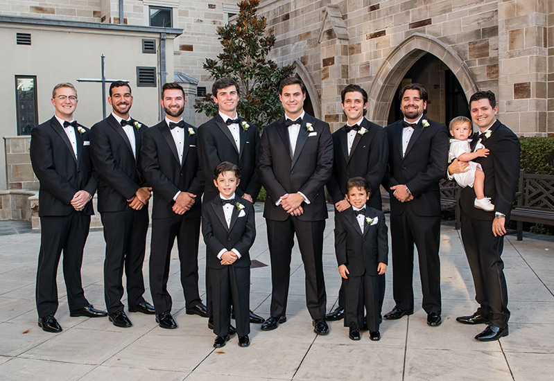 Groomsmen and groom outside of chapel wearing classic tuxedoes and black bow ties.