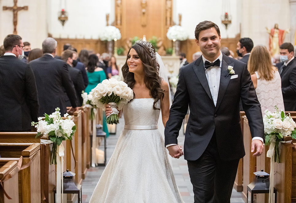 Bride and groom walk down the aisle together at their ceremony in a chapel.