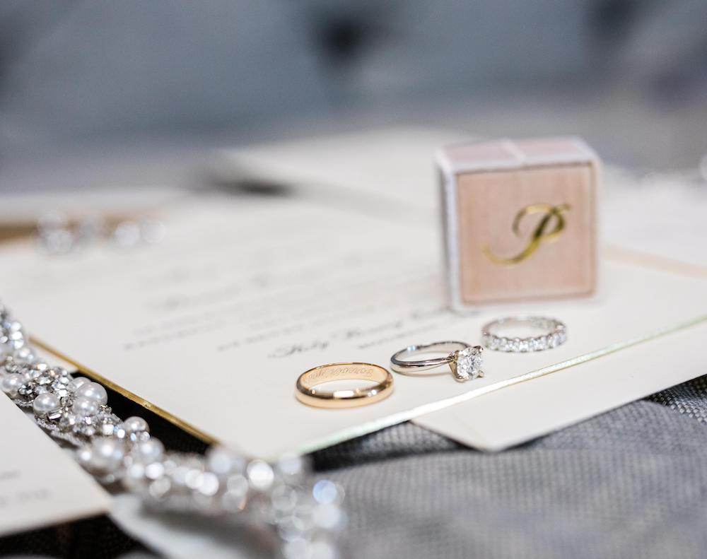 The engagement ring and wedding bands by Zadok rest on invitations from Bering's.