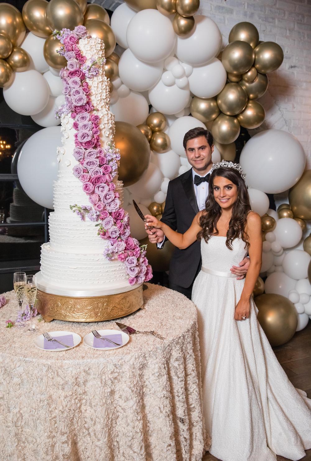 Purple flowers cascade down a seven-tier traditional wedding cake.
