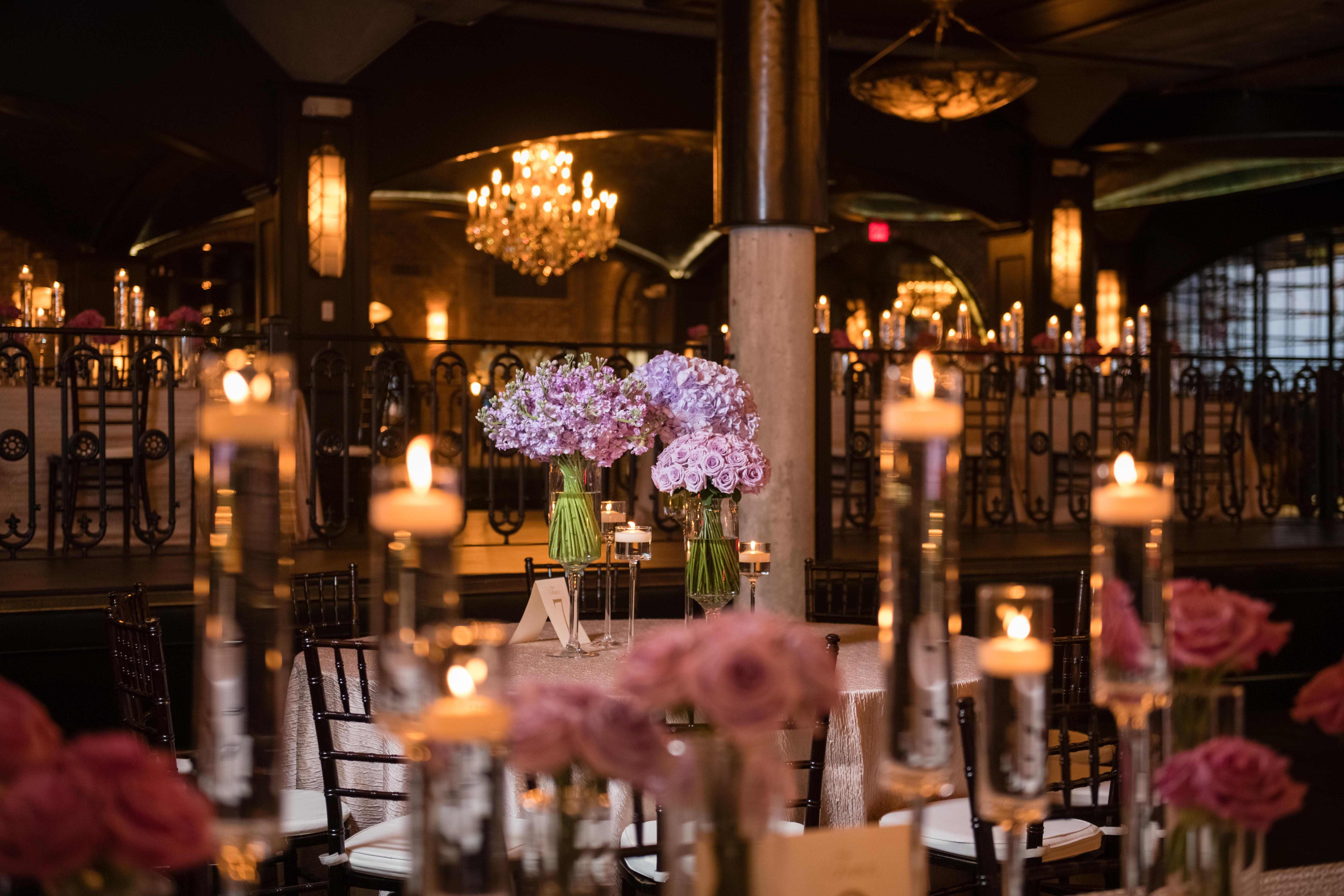 Long tables are lined with centerpiece vases of purple flowers and candles.
