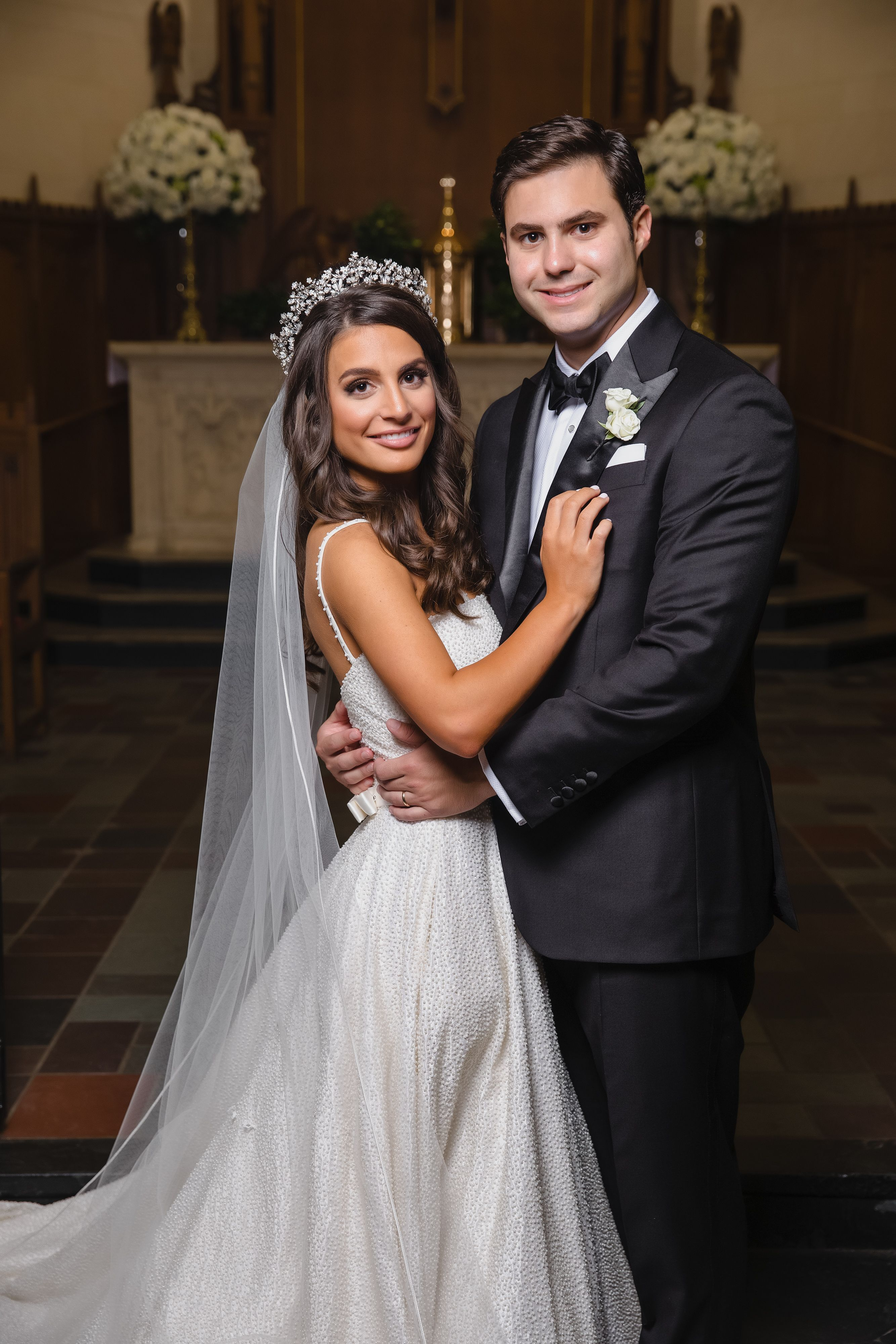 A bride, with ornate headpiece and long veil and white textured ball gown, standing groom, in all black tuxedo,  after getting married in Houston at a Catholic church.
