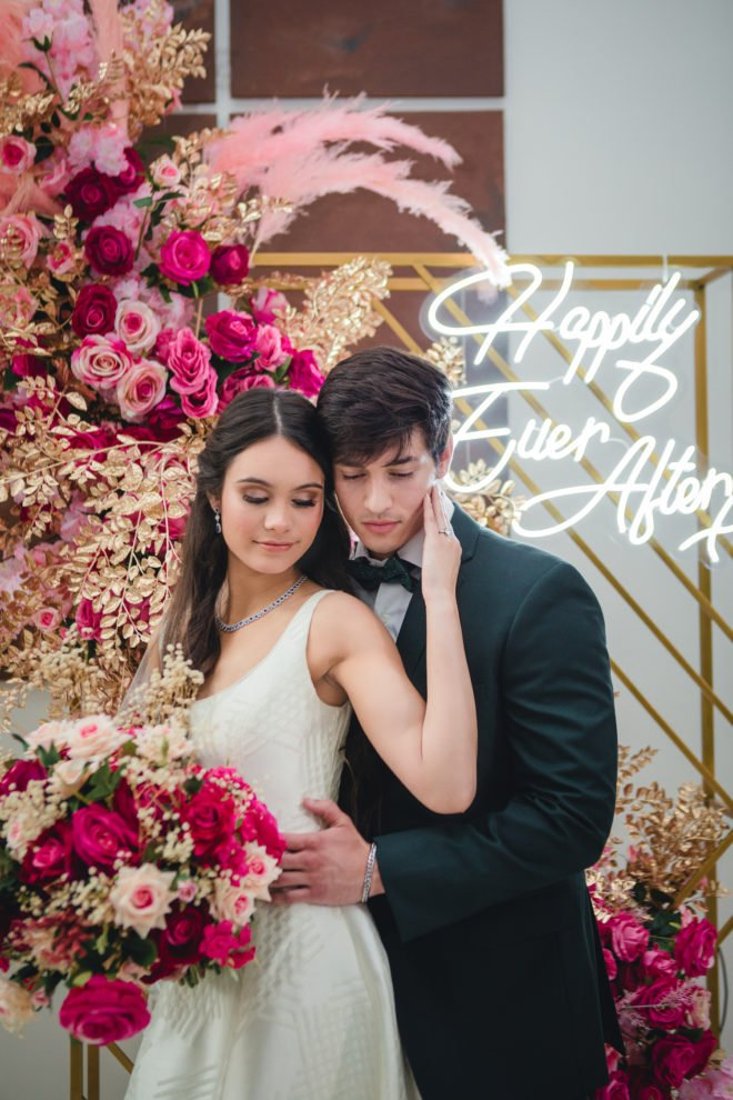 """Bride holding groom's face with gold background, lush hot pink and blush florals and lit LED sign which reads, """"Happily Ever After""""."""