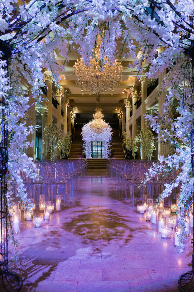 Wisteria covered arch leading to ceremony aisle with glowing candles, lavender colored uplighting and white acrylic ghost chairs designed by Plants N' Petals at the Corinithian Houston.