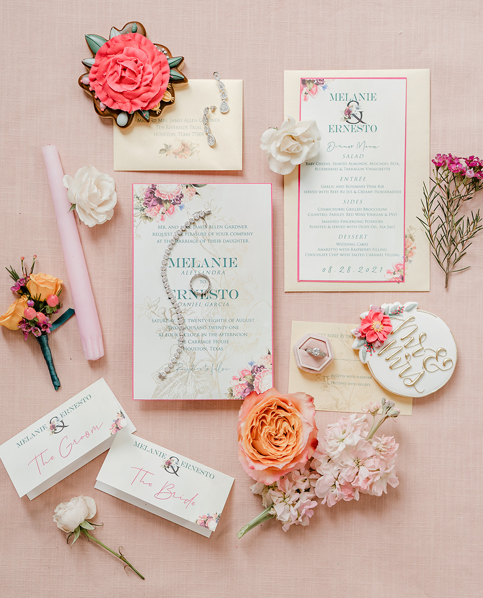 White invitations with teal lettering and floral designs on them with hydrangea stems, orange roses, and white carnations around them.