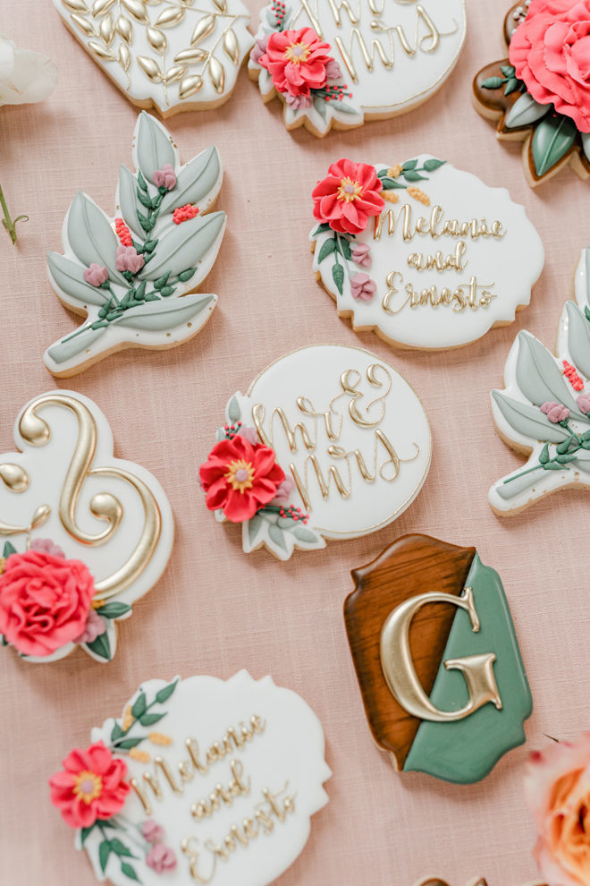 """Custom iced cookies shaped with gold calligraphy style lettering that reads """"Mr."""" and """"Mrs."""", the letter """"G"""" and """"Melanie and Ernesto"""" with purple and dark pink flowers provided by Sift and Swirl for a wedding styled shoot at The Carriage House wedding venue."""