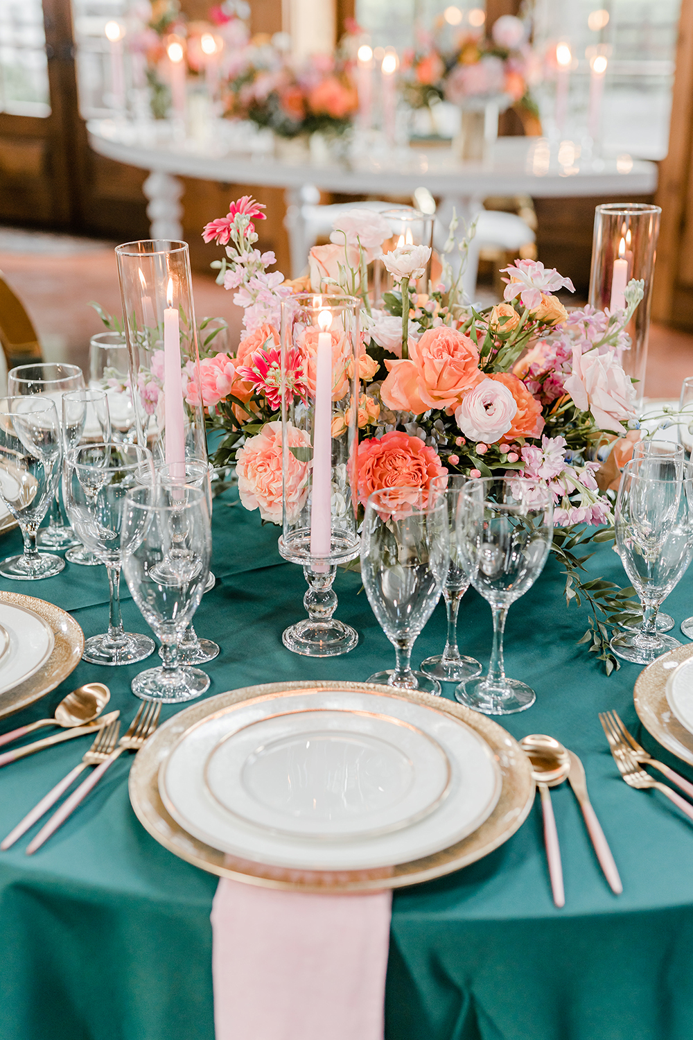 Pink lit tapered candles sit atop of a table that is adorned with emerald linens and soft pink napkins, crystal glassware, and floral decor.