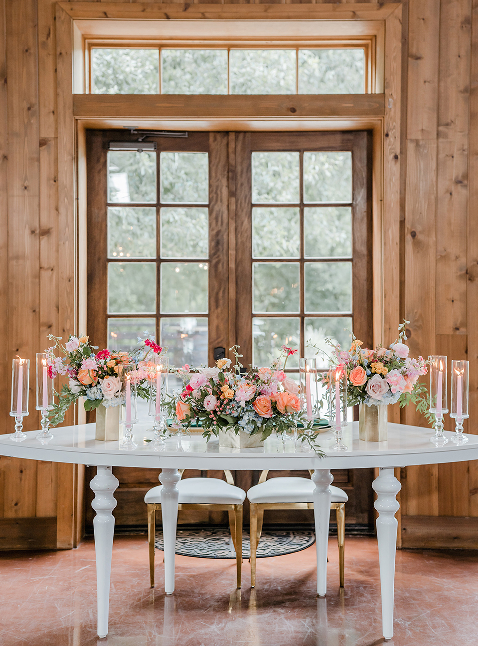 White table adorned with pink, orange, and light blue florals that include hydrangeas, roses, and peonies. Pink lit tapered candles sit atop of the table with a wooden window door behind inside of The Carriage House wedding venue in Conroe, Texas.