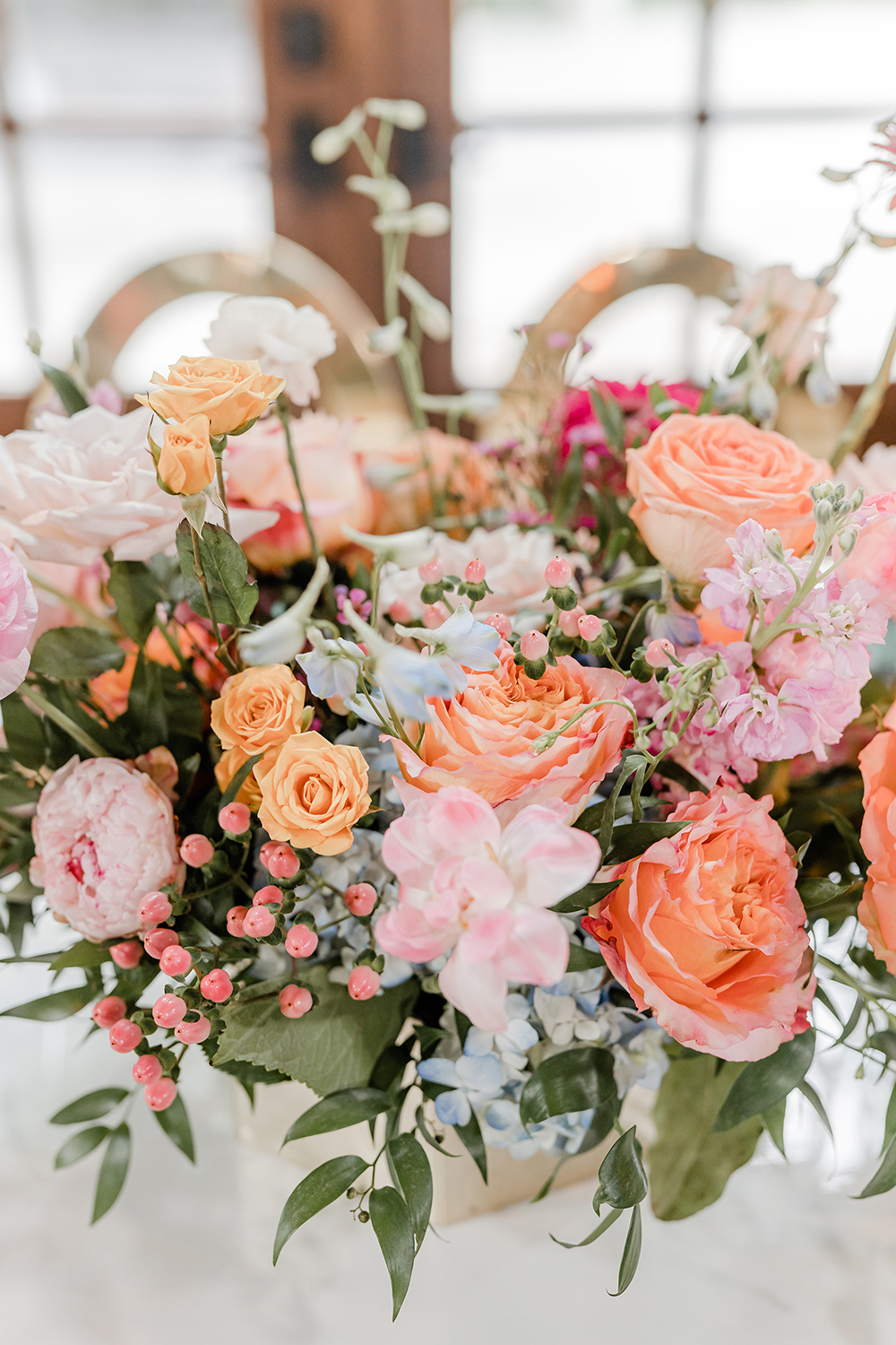 A floral arrangement made up of Silver dollar Eucalyptus, Huckleberry, Italian and Isralie Ruscus, Free Spirit Roses, Sweet Eskimo Roses, LightBlue Delphinium, Raspberry Wax Flowers, Pink Stock, Coral Hyperium Berries, and Light Blue Hydrangea.