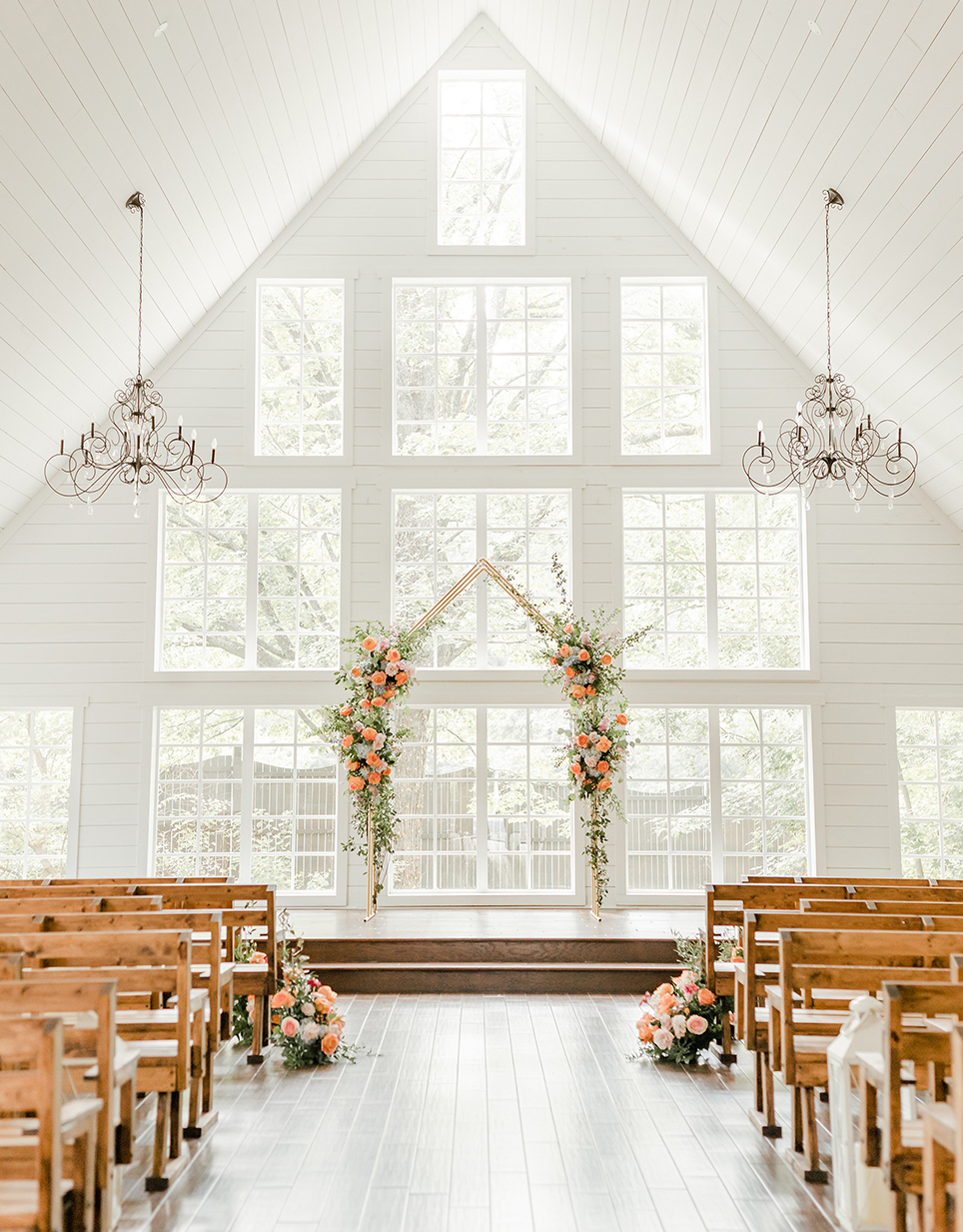 Interior of a white washed chapel with two hanging chandeliers, wooden pews flanking the aisle and a fresh floral and greenery adorned arch in front of a wall of large square and rectangle shaped windows at The Carriage House in Conroe, Texas.